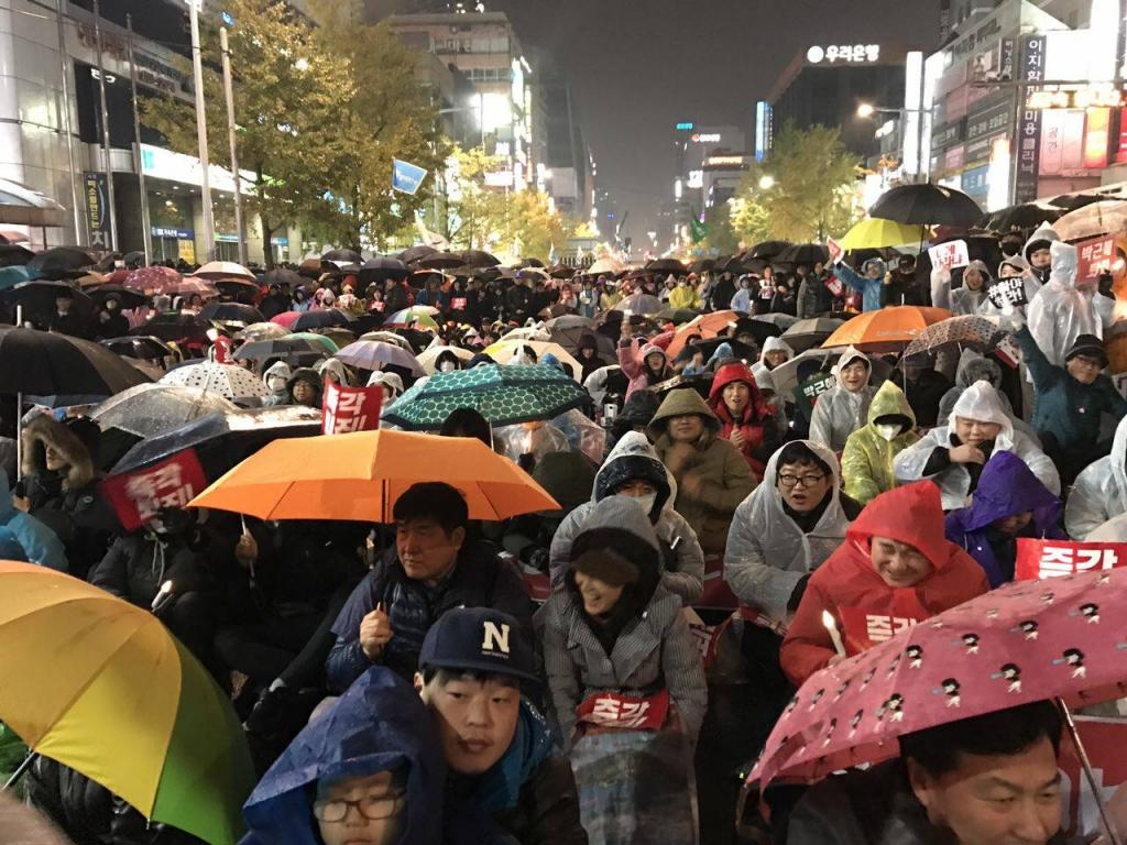 細雨紛飛的廣場上,民眾或站或坐,站立在兩旁的民眾約為席地而坐的3倍之多。圖/Lee Ji Eun