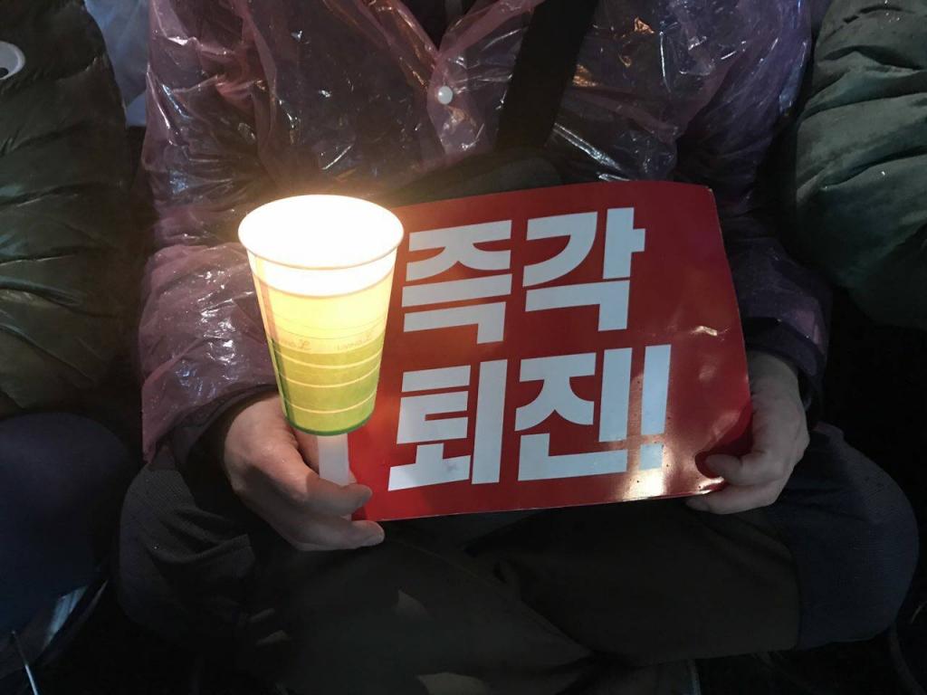 """靜坐市民身穿輕便雨衣,一手拿著紙杯做的燭臺,一手緊掐""""立馬下臺"""" (즉각 퇴진) 的紙板。圖/Lee Ji Eun"""