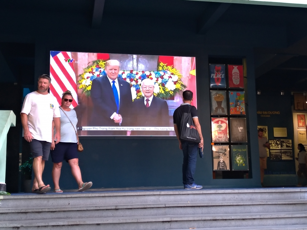 川金會期間,越戰遺跡博物館大螢幕播放現場實況。川金會不僅越南人關注,來到越南的國外觀光客也感覺身歷其境,參與了這歷史性的一刻。圖/林智恩。